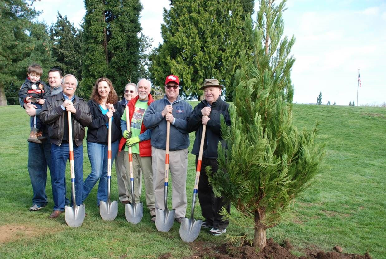 A group of people with shovels planting a tree
