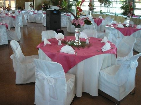 Chairs with white covers and tables with red table